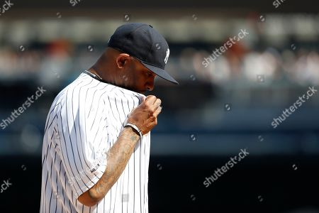New York Yankees' CC Sabathia reacts after watching a video on the stadium scoreboard before a baseball game Toronto Blue Jays, in New York