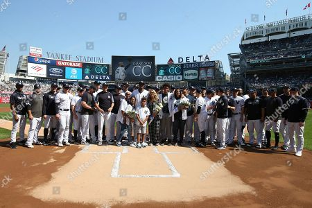 New York Yankees' CC Sabathia, center, surrounded by family and teammates, is honored before a baseball game against the Toronto Blue Jays, in New York