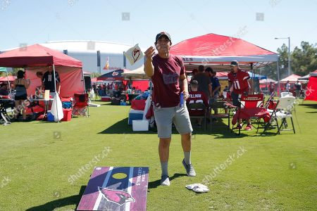 Arizona Cardinals fan Mike Henry plays cornhole prior to an NFL football game against the Carolina Panthers, in Glendale, Ariz
