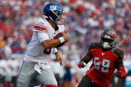 Stock Image of New York Giants quarterback Daniel Jones (8) runs at Tampa Bay Buccaneers linebacker Shaquil Barrett (58) during the first half of an NFL football game, in Tampa, Fla