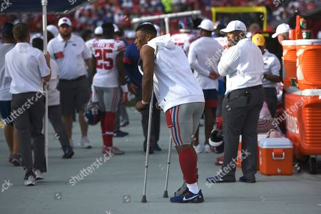 New York Giants running back Saquon Barkley stands on crutches against the Tampa Bay Buccaneers during the second half of an NFL football game, in Tampa, Fla