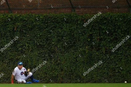 Chicago Cubs center fielder Albert Almora Jr. misses a triple hit by St. Louis Cardinals' Jose Martinez during the ninth inning of a baseball game, in Chicago
