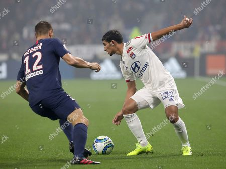 Lyon's Houssem Aouar, right vies for the ball with PSG's Thomas Meunier during the French League 1 soccer match between Lyon and Paris SG, at the Stade de Lyon in Decines, outside Lyon, France