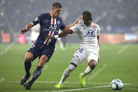Lyon's Youssouf Kone, right, shields the ball from PSG's Thomas Meunier during the French League 1 soccer match between Lyon and Paris SG, at the Stade de Lyon in Decines, outside Lyon, France
