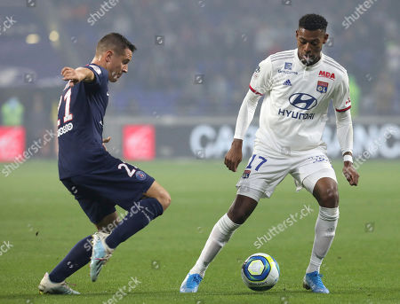 Lyon's Jeff Reine-Adelaide, right, vies for the ball with PSG's Ander Herrera during the French League 1 soccer match between Lyon and Paris SG, at the Stade de Lyon in Decines, outside Lyon, France