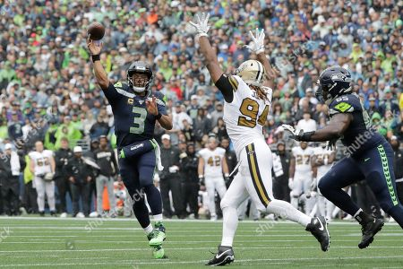 Cameron Jordan, Russell Wilson. Seattle Seahawks quarterback Russell Wilson (3) throws a touchdown pass as New Orleans Saints' Cameron Jordan defends during the first half of an NFL football game, in Seattle