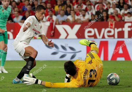 Sevilla's forward Javier 'Chicharito' Hernandez (L) and Real Madrid's goalkeeper Thibaut Courtois (R) in action during the Spanish LaLiga match between Sevilla FC and Real Madrid CF at Ramon Sanchez Pizjuan stadium in Seville, Andalusia, Spain, 22 September 2019.