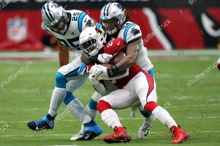 Carolina Panthers cornerback Javien Elliott (23) is tackled by Carolina Panthers outside linebacker Shaq Thompson (54) and strong safety Eric Reid (25) during the first half of an NFL football game, in Glendale, Ariz