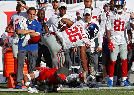 New York Giants running back Saquon Barkley (26) gets hit by Tampa Bay Buccaneers safety Mike Edwards (34) during the first half of an NFL football game, in Tampa, Fla. Barkley left the game