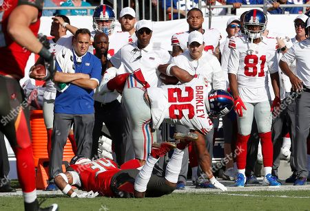 New York Giants running back Saquon Barkley (26) gets hit by Tampa Bay Buccaneers safety Mike Edwards during the first half of an NFL football game, in Tampa, Fla. Barkley left the game