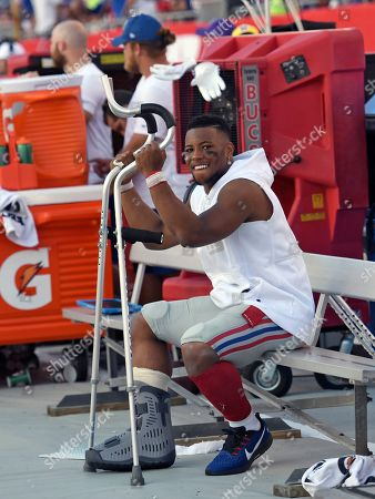 New York Giants running back Saquon Barkley smiles as he sits on the bench during the second half of an NFL football game against the Tampa Bay Buccaneers, in Tampa, Fla. Barkley was injured in the first half
