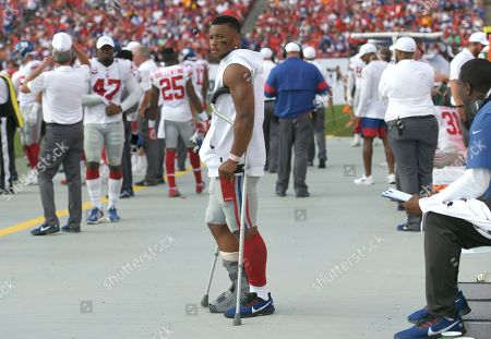 New York Giants running back Saquon Barkley stands on crutches in the bench area after getting injured against the Tampa Bay Buccaneers during the first half of an NFL football game, in Tampa, Fla