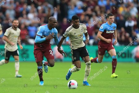 West Ham's Angelo Ogbonna challenges Manchester United's Marcus Rashford for the ball during the English Premier League soccer match between West Ham United and Manchester United at the London City Stadium in London, England, in London, England