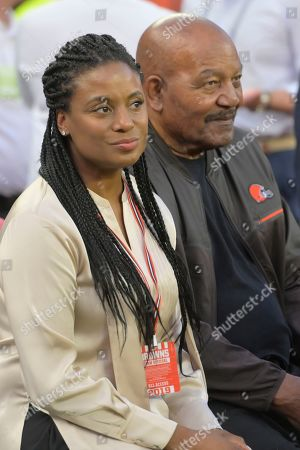 Former Cleveland Browns running back Jim Brown and his wife, Monique Brown, sit on a bench before an NFL football game between the Los Angeles Rams and the Cleveland Browns, in Cleveland. The Rams won 20-13