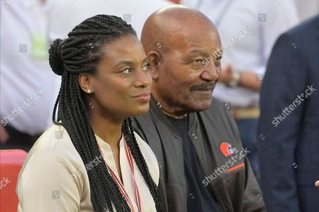 Stock Image of Former Cleveland Browns running back Jim Brown and his wife, Monique Brown, sit on a bench before an NFL football game between the Los Angeles Rams and the Cleveland Browns, in Cleveland. The Rams won 20-13