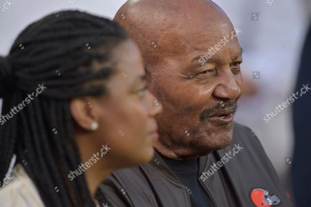Stock Photo of Former Cleveland Browns running back Jim Brown and his wife, Monique Brown, sit on a bench before an NFL football game between the Los Angeles Rams and the Cleveland Browns, in Cleveland. The Rams won 20-13