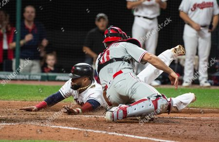 Cleveland Indians' Carlos Santana, left, slides safely into home plate ahead of the tag of Philadelphia Phillies' J.T. Realmuto after a three-run double by Yasiel Puig off Cole Irvin during the seventh inning of a baseball game in Cleveland