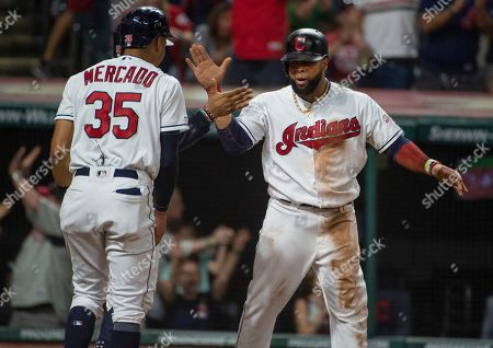 Cleveland Indians' Oscar Mercado, left, celebrates with Carlos Santana after they scored on a thee-run double by Yasiel Puig off Philadelphia Phillies relief pitcher Cole Irvin during the seventh inning of a baseball game in Cleveland
