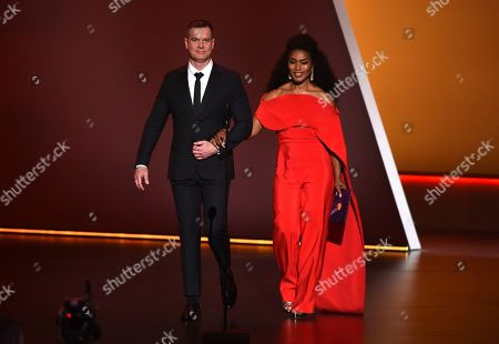 Peter Krause, Angela Bassett. Peter Krause, left, and Angela Bassett walk onstage at the 71st Primetime Emmy Awards, at the Microsoft Theater in Los Angeles