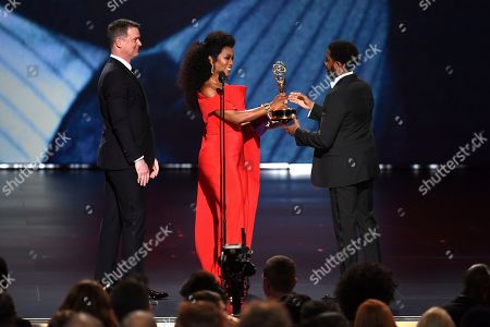 """Angela Bassett, Peter Krause, Jharrel Jerome. Jharrel Jerome, right, accepts the award for outstanding lead actor in a limited series or movie for """"When They See Us"""" as Angela Bassett and Peter Krause look on at the 71st Primetime Emmy Awards, at the Microsoft Theater in Los Angeles"""