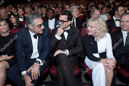 Eugene Levy, Dan Levy, Catherine O'Hara. Eugene Levy, from left, Dan Levy, and Catherine O'Hara speak in the audience at the 71st Primetime Emmy Awards, at the Microsoft Theater in Los Angeles
