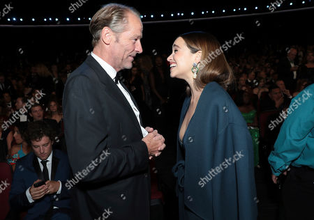 Iain Glen, Emilia Clarke. Iain Glen, left, and Emilia Clarke speak in the audience at the 71st Primetime Emmy Awards, at the Microsoft Theater in Los Angeles
