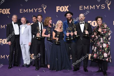"""Johan Renck, Craig Mazin. Johan Renck, third from right, winner of the award for outstanding directing for a limited series, movie or special, Craig Mazin, second from right, winner of the award for outstanding writing for a limited series or movie, and the cast and crew of """"Chernobyl"""" winners of the award for outstanding limited series or movie pose in the press room at the 71st Primetime Emmy Awards, at the Microsoft Theater in Los Angeles"""