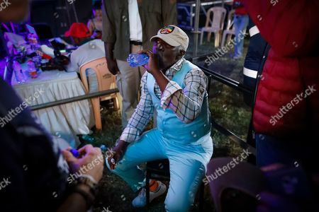 Ivorian reggae legend Seydou Kone, better known by his artistic name Alpha Blondy, takes a drink of water backstage before he is called back for an encore in Nairobi, Kenya, 22 September 2019. The 66-year-old African reggae legend headlined the Kenyan music event Koroga Festival.
