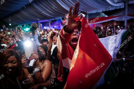 A young boy holds up an flag and cheers as Ivorian reggae legend Seydou Kone, better known by his artistic name Alpha Blondy, performs on stage in Nairobi, Kenya, 22 September 2019. The 66-year-old African reggae legend headlined the Kenyan music event Koroga Festival.
