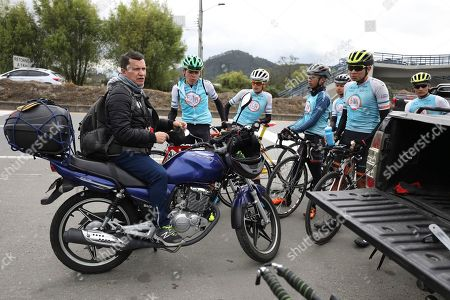 Wilson Sandoval, left, the team manager of the Esteban Chaves Foundation, talks to his cyclists after a training session in Puente Piedra near Bogota, Colombia, . Sandoval said his teams require any aspiring cyclist that wants a tryout to take an obligatory doping test