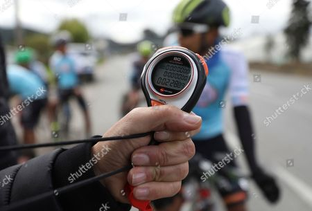 Wilson Sandoval, the manager of the Esteban Chaves Foundation cycling team, clocks his cyclists during time trial training in Puente Piedra near in Bogota, Colombia, . Although the team's cyclists are clean, Colombian cycling veteran Juan Pablo Villegas said in 2015 that the widespread use of performance enhancing drugs is driven by the desperate economic situation many of the country's 5,000 professional cyclists find themselves in. With little prize money available and most professional teams offering only minimal support, many will do whatever it takes to survive in the sport