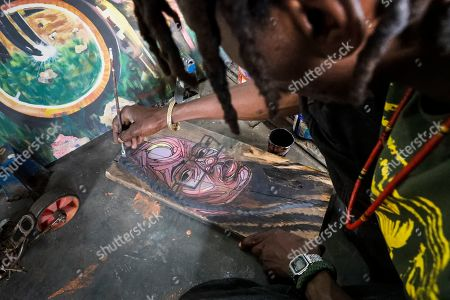 Kenneth Otieno, also known by his artistic name Kaymist4, works on his painting in an abandoned train carriage-turned art studio of the Bombsquad, or BSQ Crew, next to the Nairobi Railway Museum in central Nairobi, Kenya, 20 August 2019 (issued 23 September 2019). Graffiti artists of BSQ Crew, originally started by three founding members, have been working out of an abandoned train carriage they rented from the Railway museum management which they turned into an art studio. Brian Musasia, also known by his artistic name Msale, is one of the original BSQ members. The twenty-six-year-old former art student says that at times, he struggles financially as a street artist in Kenya. Painting on a used pre-painted fabric he used in his house as a window curtain, Msale says the idea to paint over it came when he had no money to buy a canvas. 'It is our responsibility as (African) artists to tell a different story about Africa than what you have been told or been learning - the real stories we live'. Another founding member Bebeto Ochieng, or Thufu-B, says he believes in the role the art plays in society. 'We believe art is a weapon for change. And the new generation of Kenyan artists will shake the whole of Nairobi', the young artist says enthusiastically. Although many artists in Kenya struggle to earn enough for a living and it is rarely seen as a proper profession, yet the art scene in Nairobi has been growing in recent years with an increasing number of artists who gain recognition abroad.