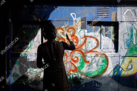 Kimberly Davina, a nineteen-year-old Kenyan graffiti artist from the artist group Spray Uzi Crew, spray paints on the exterior of an abandoned train carriage-turned art studio next to where artists from the Bombsquad, or BSQ Crew work, at the Nairobi Railway Museum in central Nairobi, Kenya, 20 August 2019 (issued 23 September 2019). Graffiti artists of BSQ Crew, originally started by three founding members, have been working out of an abandoned train carriage they rented from the Railway museum management which they turned into an art studio. Brian Musasia, also known by his artistic name Msale, is one of the original BSQ members. The twenty-six-year-old former art student says that at times, he struggles financially as a street artist in Kenya. Painting on a used pre-painted fabric he used in his house as a window curtain, Msale says the idea to paint over it came when he had no money to buy a canvas. 'It is our responsibility as (African) artists to tell a different story about Africa than what you have been told or been learning - the real stories we live'. Another founding member Bebeto Ochieng, or Thufu-B, says he believes in the role the art plays in society. 'We believe art is a weapon for change. And the new generation of Kenyan artists will shake the whole of Nairobi', the young artist says enthusiastically. Although many artists in Kenya struggle to earn enough for a living and it is rarely seen as a proper profession, yet the art scene in Nairobi has been growing in recent years with an increasing number of artists who gain recognition abroad.