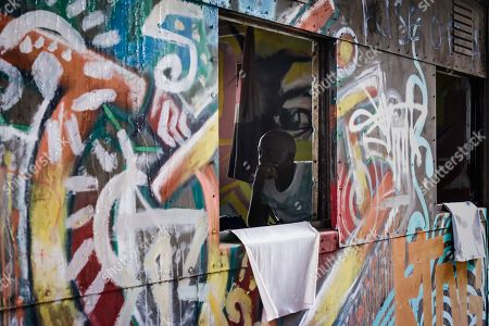 A man looks on inside an abandoned train carriage-turned art studio of an artist group Spray Uzi Crew, next to where artists from the Bombsquad, or BSQ Crew, work at the Nairobi Railway Museum in central Nairobi, Kenya, 20 August 2019 (issued 23 September 2019). Graffiti artists of BSQ Crew, originally started by three founding members, have been working out of an abandoned train carriage they rented from the Railway museum management which they turned into an art studio. Brian Musasia, also known by his artistic name Msale, is one of the original BSQ members. The twenty-six-year-old former art student says that at times, he struggles financially as a street artist in Kenya. Painting on a used pre-painted fabric he used in his house as a window curtain, Msale says the idea to paint over it came when he had no money to buy a canvas. 'It is our responsibility as (African) artists to tell a different story about Africa than what you have been told or been learning - the real stories we live'. Another founding member Bebeto Ochieng, or Thufu-B, says he believes in the role the art plays in society. 'We believe art is a weapon for change. And the new generation of Kenyan artists will shake the whole of Nairobi', the young artist says enthusiastically. Although many artists in Kenya struggle to earn enough for a living and it is rarely seen as a proper profession, yet the art scene in Nairobi has been growing in recent years with an increasing number of artists who gain recognition abroad.