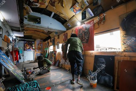 Kenneth Otieno (L), also known by his artistic name Kaymist4, and Bebeto Ochieng, or Thufu-B (R), work in an abandoned train carriage-turned art studio of the Bombsquad, or BSQ Crew, next to the Nairobi Railway Museum in central Nairobi, Kenya, 20 August 2019 (issued 23 September 2019). Graffiti artists of BSQ Crew, originally started by three founding members, have been working out of an abandoned train carriage they rented from the Railway museum management which they turned into an art studio. Brian Musasia, also known by his artistic name Msale, is one of the original BSQ members. The twenty-six-year-old former art student says that at times, he struggles financially as a street artist in Kenya. Painting on a used pre-painted fabric he used in his house as a window curtain, Msale says the idea to paint over it came when he had no money to buy a canvas. 'It is our responsibility as (African) artists to tell a different story about Africa than what you have been told or been learning - the real stories we live'. Another founding member Bebeto Ochieng, or Thufu-B, says he believes in the role the art plays in society. 'We believe art is a weapon for change. And the new generation of Kenyan artists will shake the whole of Nairobi', the young artist says enthusiastically. Although many artists in Kenya struggle to earn enough for a living and it is rarely seen as a proper profession, yet the art scene in Nairobi has been growing in recent years with an increasing number of artists who gain recognition abroad.