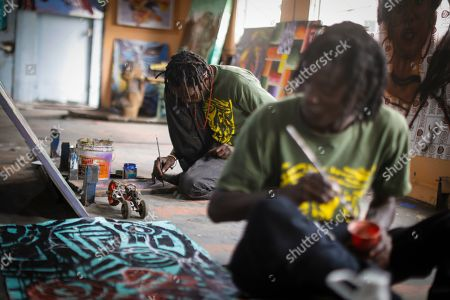 Kenneth Otieno (L), also known by his artistic name Kaymist4, works on his painting in an abandoned train carriage-turned art studio of the Bombsquad, or BSQ Crew, next to the Nairobi Railway Museum in central Nairobi, Kenya, 20 August 2019 (issued 23 September 2019). Graffiti artists of BSQ Crew, originally started by three founding members, have been working out of an abandoned train carriage they rented from the Railway museum management which they turned into an art studio. Brian Musasia, also known by his artistic name Msale, is one of the original BSQ members. The twenty-six-year-old former art student says that at times, he struggles financially as a street artist in Kenya. Painting on a used pre-painted fabric he used in his house as a window curtain, Msale says the idea to paint over it came when he had no money to buy a canvas. 'It is our responsibility as (African) artists to tell a different story about Africa than what you have been told or been learning - the real stories we live'. Another founding member Bebeto Ochieng, or Thufu-B, says he believes in the role the art plays in society. 'We believe art is a weapon for change. And the new generation of Kenyan artists will shake the whole of Nairobi', the young artist says enthusiastically. Although many artists in Kenya struggle to earn enough for a living and it is rarely seen as a proper profession, yet the art scene in Nairobi has been growing in recent years with an increasing number of artists who gain recognition abroad.