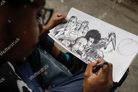 An artist works on his sketch in front of an abandoned train carriage-turned art studio of the Bombsquad, or BSQ Crew, next to the Nairobi Railway Museum in central Nairobi, Kenya, 20 August 2019 (issued 23 September 2019). Graffiti artists of BSQ Crew, originally started by three founding members, have been working out of an abandoned train carriage they rented from the Railway museum management which they turned into an art studio. Brian Musasia, also known by his artistic name Msale, is one of the original BSQ members. The twenty-six-year-old former art student says that at times, he struggles financially as a street artist in Kenya. Painting on a used pre-painted fabric he used in his house as a window curtain, Msale says the idea to paint over it came when he had no money to buy a canvas. 'It is our responsibility as (African) artists to tell a different story about Africa than what you have been told or been learning - the real stories we live'. Another founding member Bebeto Ochieng, or Thufu-B, says he believes in the role the art plays in society. 'We believe art is a weapon for change. And the new generation of Kenyan artists will shake the whole of Nairobi', the young artist says enthusiastically. Although many artists in Kenya struggle to earn enough for a living and it is rarely seen as a proper profession, yet the art scene in Nairobi has been growing in recent years with an increasing number of artists who gain recognition abroad.