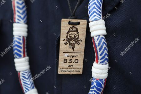 A graffiti art enthusiast wears a necklace featuring BSQ Crew's logo during an  exhibition by Kenyatta University art students who finished their internship programme with BSQ at the Nairobi Railway Museum in central Nairobi, Kenya, 07 September 2019 (issued 23 September 2019). Graffiti artists of BSQ Crew, originally started by three founding members, have been working out of an abandoned train carriage they rented from the Railway museum management which they turned into an art studio. Brian Musasia, also known by his artistic name Msale, is one of the original BSQ members. The twenty-six-year-old former art student says that at times, he struggles financially as a street artist in Kenya. Painting on a used pre-painted fabric he used in his house as a window curtain, Msale says the idea to paint over it came when he had no money to buy a canvas. 'It is our responsibility as (African) artists to tell a different story about Africa than what you have been told or been learning - the real stories we live'. Another founding member Bebeto Ochieng, or Thufu-B, says he believes in the role the art plays in society. 'We believe art is a weapon for change. And the new generation of Kenyan artists will shake the whole of Nairobi', the young artist says enthusiastically. Although many artists in Kenya struggle to earn enough for a living and it is rarely seen as a proper profession, yet the art scene in Nairobi has been growing in recent years with an increasing number of artists who gain recognition abroad.