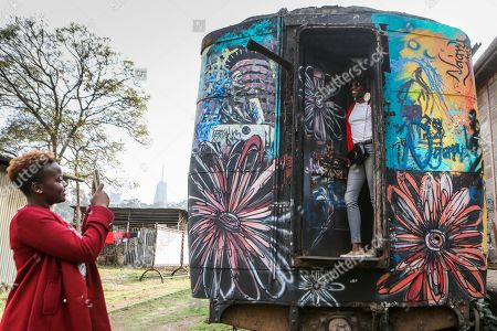 Visitors take photos on an abandoned train carriage-turned art studio during an exhibition by Kenyatta University art students who finished their internship programme with Bombsquad, or BSQ Crew, at the Nairobi Railway Museum in central Nairobi, Kenya, 07 September 2019 (issued 23 September 2019). Graffiti artists of BSQ Crew, originally started by three founding members, have been working out of an abandoned train carriage they rented from the Railway museum management which they turned into an art studio. Brian Musasia, also known by his artistic name Msale, is one of the original BSQ members. The twenty-six-year-old former art student says that at times, he struggles financially as a street artist in Kenya. Painting on a used pre-painted fabric he used in his house as a window curtain, Msale says the idea to paint over it came when he had no money to buy a canvas. 'It is our responsibility as (African) artists to tell a different story about Africa than what you have been told or been learning - the real stories we live'. Another founding member Bebeto Ochieng, or Thufu-B, says he believes in the role the art plays in society. 'We believe art is a weapon for change. And the new generation of Kenyan artists will shake the whole of Nairobi', the young artist says enthusiastically. Although many artists in Kenya struggle to earn enough for a living and it is rarely seen as a proper profession, yet the art scene in Nairobi has been growing in recent years with an increasing number of artists who gain recognition abroad.