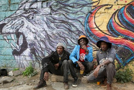 Three founding members of Bombsquad, or BSQ Crew (L-R), Kenneth Otieno, also known by his artistic name Kaymist4, Brian Musasia, or Msale, and Bebeto Ochieng, or Thufu-B, pose for a photograph in front of a mural they painted near their abandoned train carriage-turned art studio at the Nairobi Railway Museum in central Nairobi, Kenya, 07 September 2019 (issued 23 September 2019). Graffiti artists of BSQ Crew, originally started by three founding members, have been working out of an abandoned train carriage they rented from the Railway museum management which they turned into an art studio. Brian Musasia, also known by his artistic name Msale, is one of the original BSQ members. The twenty-six-year-old former art student says that at times, he struggles financially as a street artist in Kenya. Painting on a used pre-painted fabric he used in his house as a window curtain, Msale says the idea to paint over it came when he had no money to buy a canvas. 'It is our responsibility as (African) artists to tell a different story about Africa than what you have been told or been learning - the real stories we live'. Another founding member Bebeto Ochieng, or Thufu-B, says he believes in the role the art plays in society. 'We believe art is a weapon for change. And the new generation of Kenyan artists will shake the whole of Nairobi', the young artist says enthusiastically. Although many artists in Kenya struggle to earn enough for a living and it is rarely seen as a proper profession, yet the art scene in Nairobi has been growing in recent years with an increasing number of artists who gain recognition abroad.