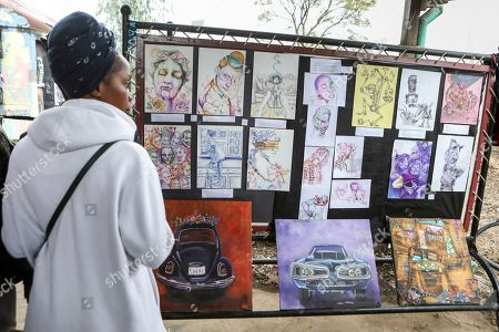 A visitor looks at artworks during an exhibition by Kenyatta University art students who finished their internship programme with BSQ at the Nairobi Railway Museum in central Nairobi, Kenya, 07 September 2019. Graffiti artists of BSQ Crew, originally started by three founding members, have been working out of an abandoned train carriage they rented from the Railway museum management which they turned into an art studio. Brian Musasia, also known by his artistic name Msale, is one of the original BSQ members. The twenty-six-year-old former art student says that at times, he struggles financially as a street artist in Kenya. Painting on a used pre-painted fabric he used in his house as a window curtain, Msale says the idea to paint over it came when he had no money to buy a canvas. 'It is our responsibility as (African) artists to tell a different story about Africa than what you have been told or been learning - the real stories we live'. Another founding member Bebeto Ochieng, or Thufu-B, says he believes in the role the art plays in society. 'We believe art is a weapon for change. And the new generation of Kenyan artists will shake the whole of Nairobi', the young artist says enthusiastically. Although many artists in Kenya struggle to earn enough for a living and it is rarely seen as a proper profession, yet the art scene in Nairobi has been growing in recent years with an increasing number of artists who gain recognition abroad.