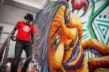 Brian Musasia, also known by his artist name Msale, walks down the stairs as he spray paints on the wall of their client, an ice cream parlor to be opened soon in Nairobi, Kenya, 07 September 2019. Graffiti artists of BSQ Crew, originally started by three founding members, have been working out of an abandoned train carriage they rented from the Railway museum management which they turned into an art studio. Brian Musasia, also known by his artistic name Msale, is one of the original BSQ members. The twenty-six-year-old former art student says that at times, he struggles financially as a street artist in Kenya. Painting on a used pre-painted fabric he used in his house as a window curtain, Msale says the idea to paint over it came when he had no money to buy a canvas. 'It is our responsibility as (African) artists to tell a different story about Africa than what you have been told or been learning - the real stories we live'. Another founding member Bebeto Ochieng, or Thufu-B, says he believes in the role the art plays in society. 'We believe art is a weapon for change. And the new generation of Kenyan artists will shake the whole of Nairobi', the young artist says enthusiastically. Although many artists in Kenya struggle to earn enough for a living and it is rarely seen as a proper profession, yet the art scene in Nairobi has been growing in recent years with an increasing number of artists who gain recognition abroad.