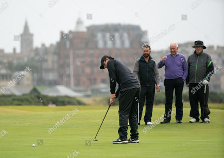 Rory McIlroy holes a putt, watched by his Dad Gerry McIlroy (purple jumper), on the 16th green at The Old Course, St. Andrews.