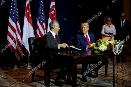 Donald Trump, Lee Hsien Loong. President Donald Trump signs memorandum of understanding with Singapore Prime Minister Lee Hsien Loong at the InterContinental Barclay hotel during the United Nations General Assembly, in New York