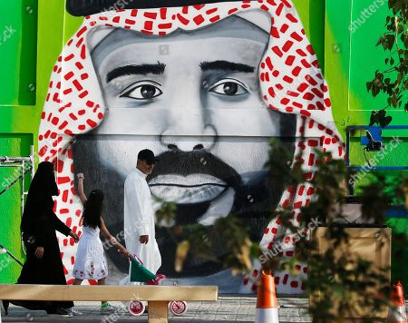 People walk in front of graffiti showing Crown Prince Mohammed bin Salman marking National Day to commemorate the unification of the country as the Kingdom of Saudi Arabia, in Riyadh, Saudi Arabia