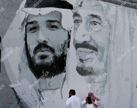 A giant banner showing Saudi King Salman, right, and Crown Prince Mohammed bin Salman, hangs at a shopping mall, marking National Day to commemorate the unification of the country as the Kingdom of Saudi Arabia, in Riyadh, Saudi Arabia