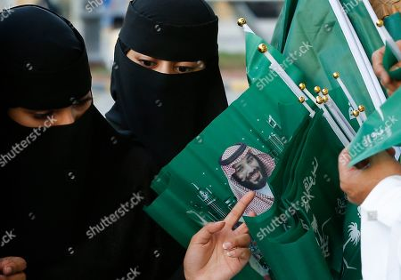 Women buy national flags with a picture of Crown Prince Mohammed bin Salman, marking National Day to commemorate the unification of the country as the Kingdom of Saudi Arabia, in Riyadh, Saudi Arabia