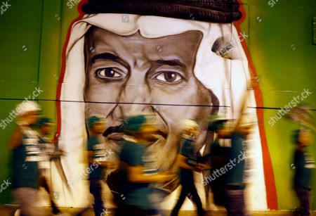 In this picture taken with low shutter speed, people walk in front of graffiti showing Saudi King Salman, marking National Day to commemorate the unification of the country as the Kingdom of Saudi Arabia, in Riyadh, Saudi Arabia