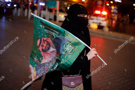 A Saudi woman holds a national flag with picture of Crown Prince Mohammed bin Salman, marking National Day to commemorate the unification of the country as the Kingdom of Saudi Arabia, in Riyadh, Saudi Arabia