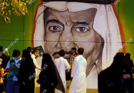 People pos§e for pictures in front of graffiti showing Saudi King Salman, marking National Day to commemorate the unification of the country as the Kingdom of Saudi Arabia, in Riyadh, Saudi Arabia
